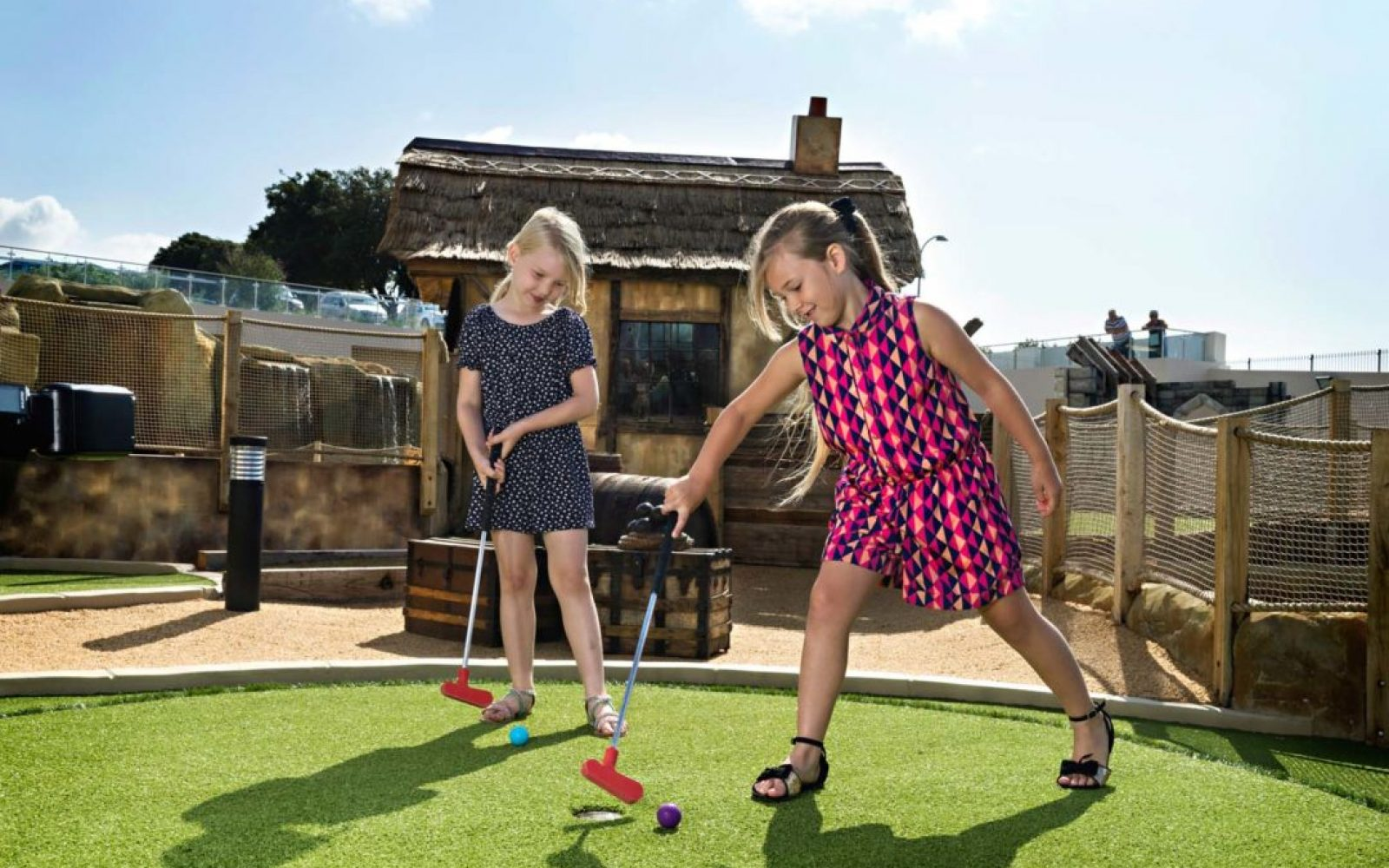 Two girls smiling and using their clubs to putt the golf ball into the hole