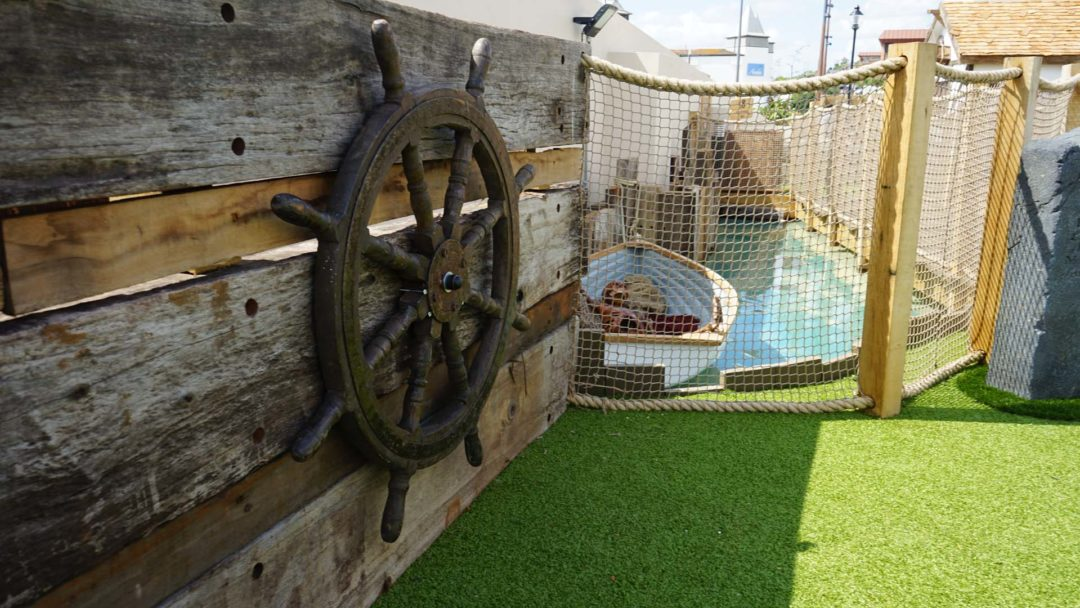 Close up of a smugglers ship wheel and boat in the water